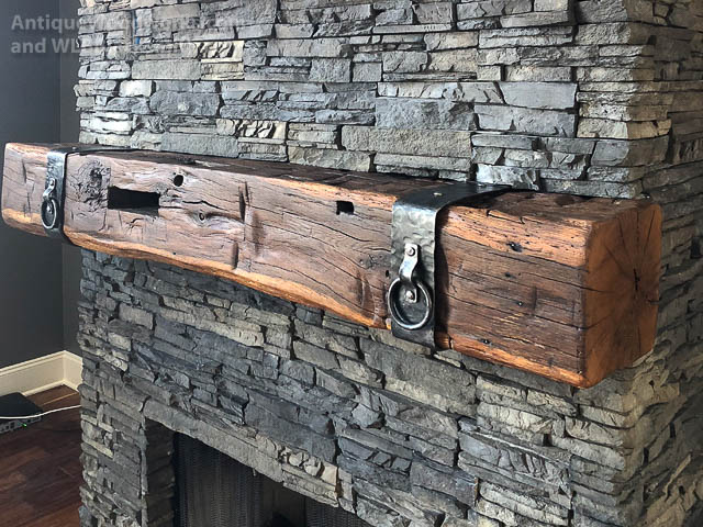 1800s vintage hand hewn mantel with hand forged iron straps and rings.