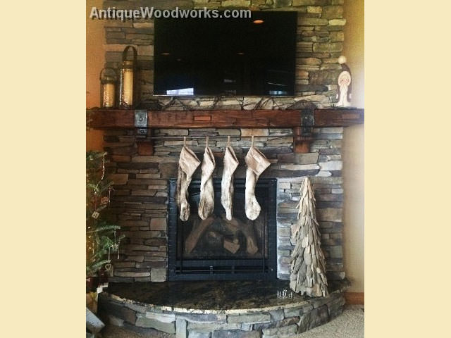 Christmas stockings hanging on rustic mantel with ironwork