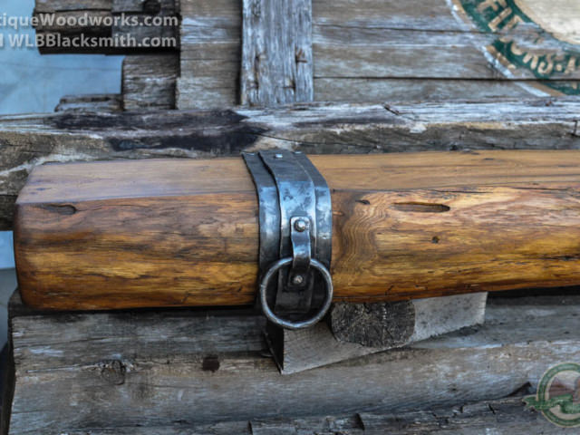 Double layer metal straps with rings applied to log cabin timber fireplace mantel.